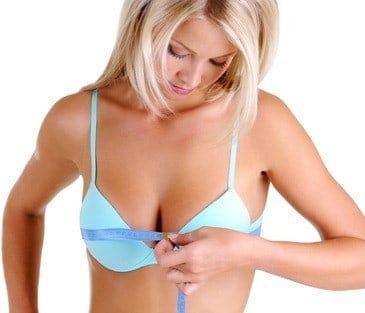 woman measures her breasts after enhancement